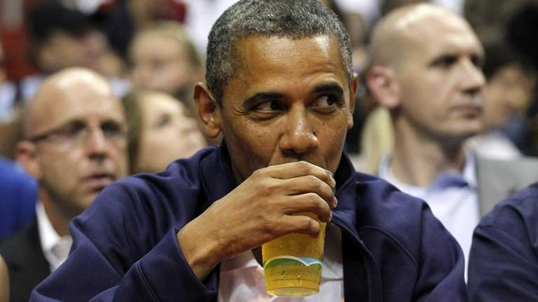 President Barack Obama sips his beer as he