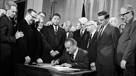 As Walter Mondale, second from right, watches, President