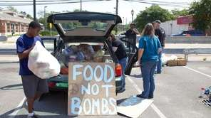 Volunteers from Food Not Bombs unload at their