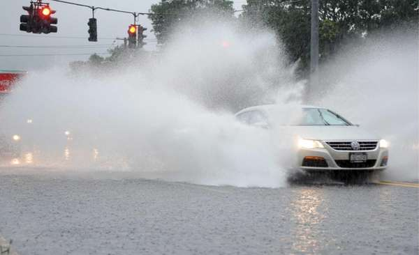 A car splashes through flooded Route 112 near