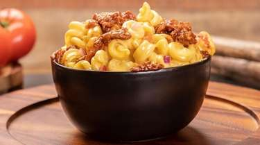 Macaroni and cheese is topped with pulled pork