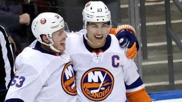 Islanders left wing Anders Lee, right, celebrates with