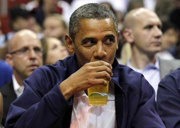 President Barack Obama sips a beer as he