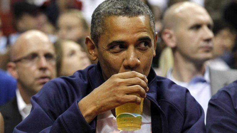 President Barack Obama sips a beer as he