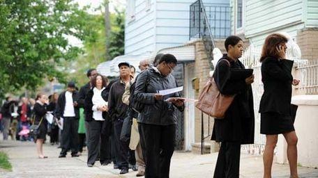 People seeking jobs wait to speak to over