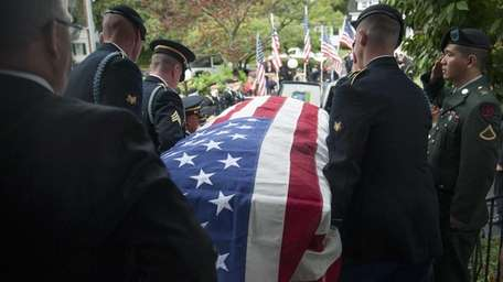 Spc. John Barbato's remains are carried from Powell