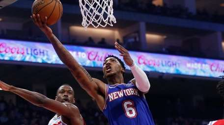 Knicks guard Elfrid Payton, center, goes to the