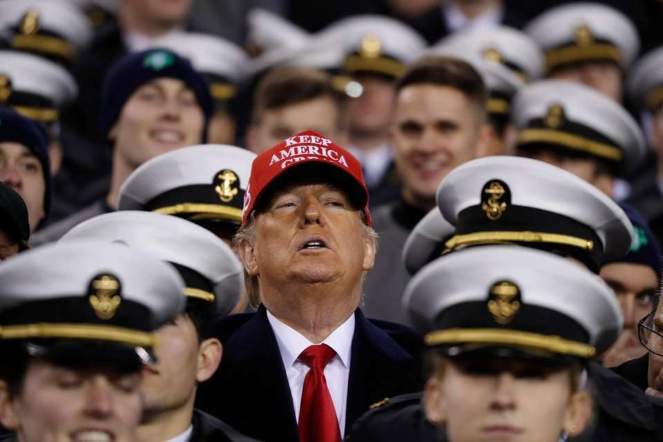President Donald Trump stands with the Navy midshipmen