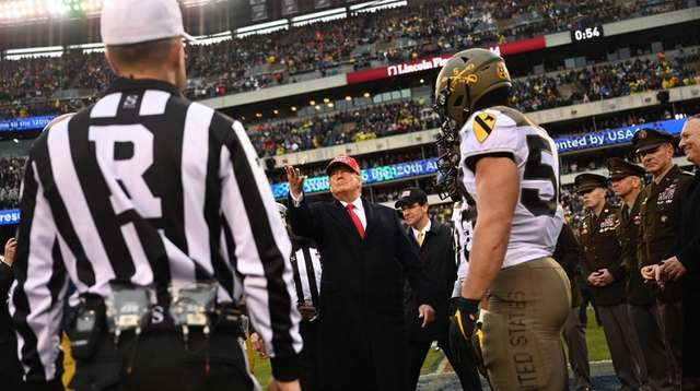 President Donald Trump tosses the coin before the