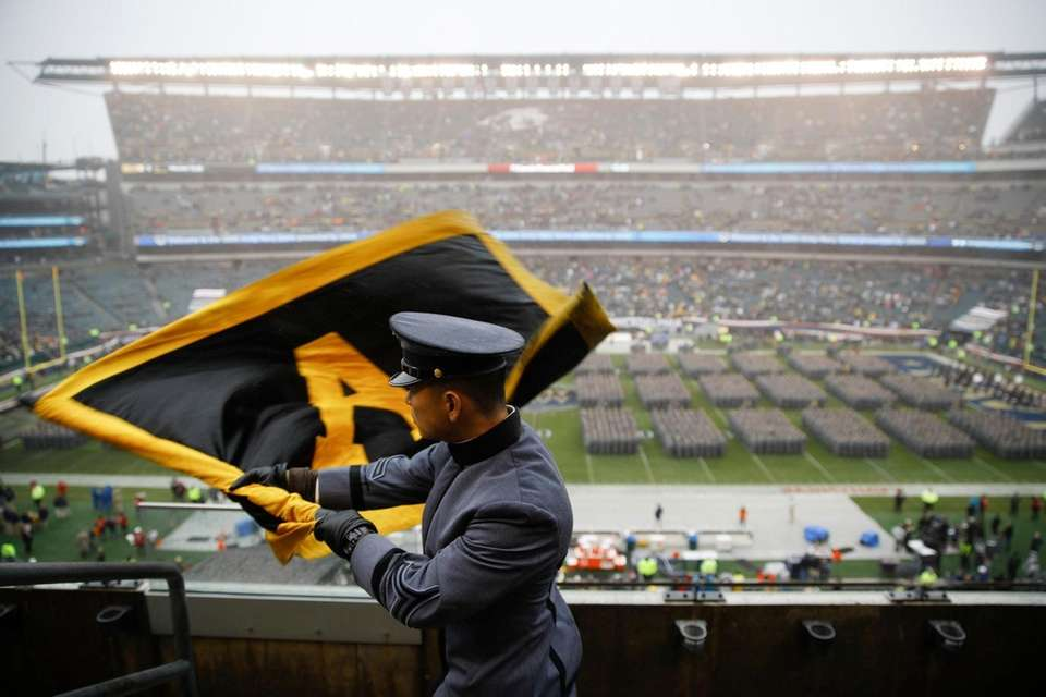 An Army cadet signals his classmates on the
