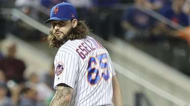 Mets relief pitcher Robert Gsellman checks the runner