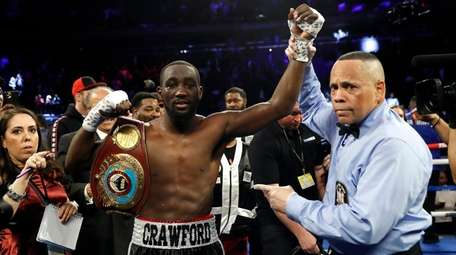 Terence Crawford has his hand raised in victory