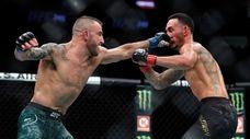 Alexander Volkanovski (L) punches UFC featherweight champion Max