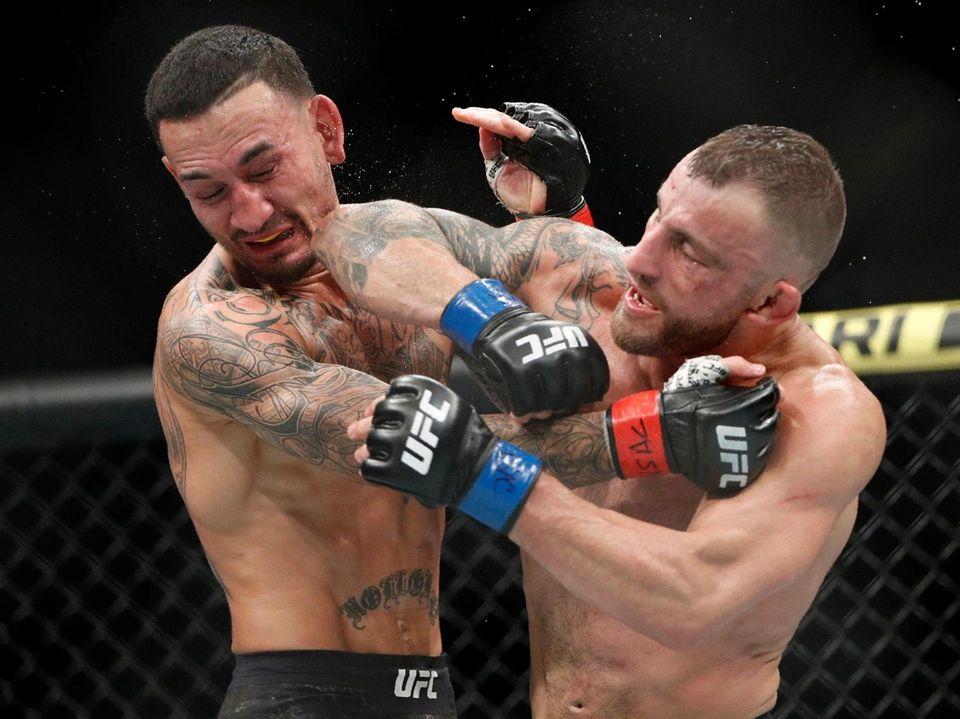 Alexander Volkanovski lands an elbow to Max Holloway