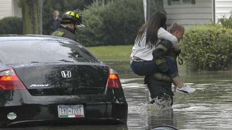 A Levittown firefighter carries Olivia Disconti, 19, of