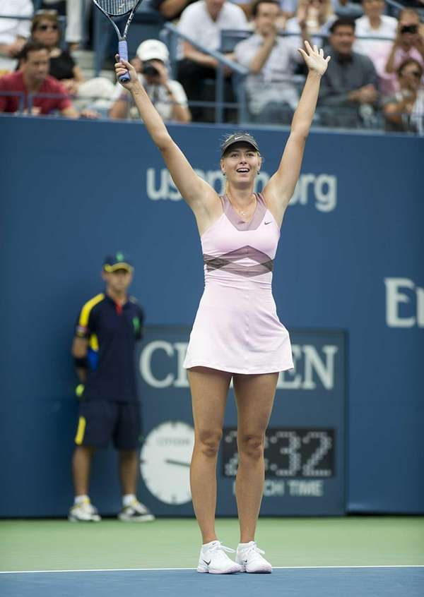 Maria Sharapova raises her arms after defeating Marion