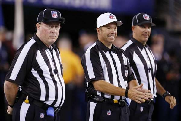 Referee Jim Core, center, gestures alongside other game