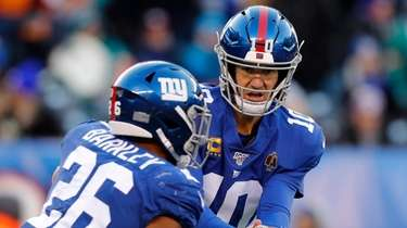Eli Manning of the Giants hands the ball