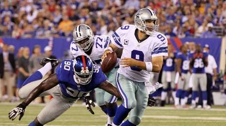 Tony Romo eludes Jason Pierre-Paulprior to throwing a