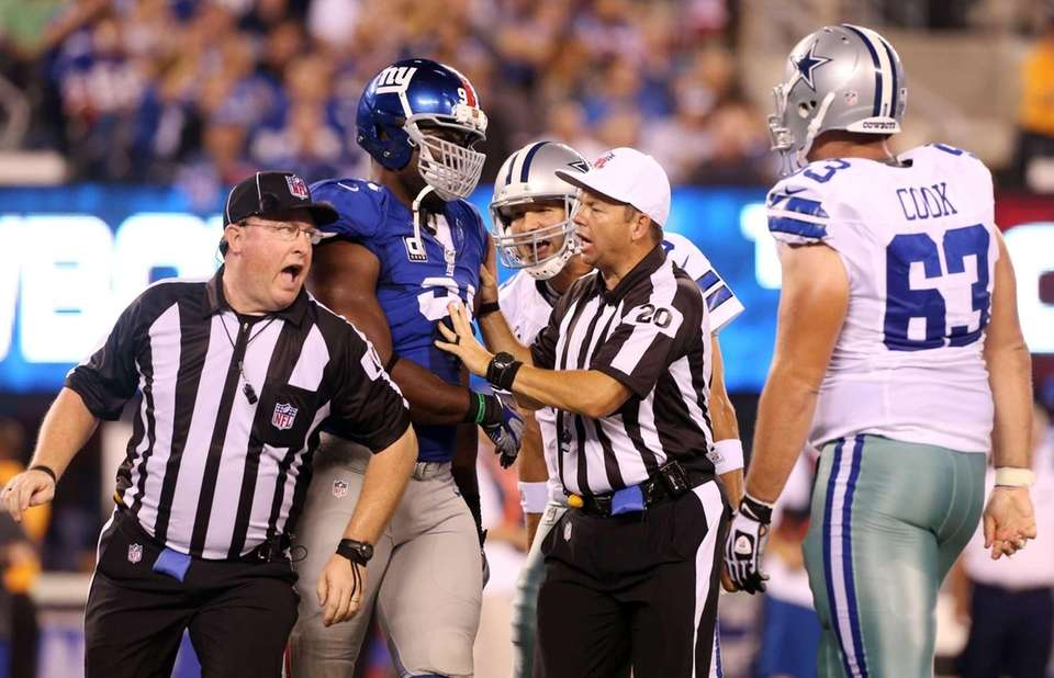 Referee Jim Core gets between Justin Tuck, Tony