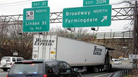 A tractor trailer stuck under a bridge on