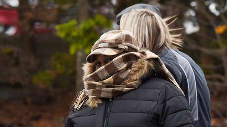 Pedestrians bundle up against the wind and cold