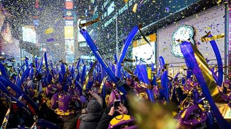 Falling confetti helps revelers ring in the New