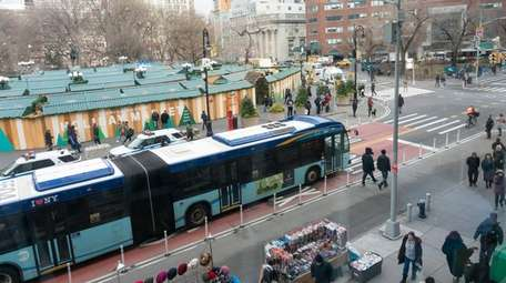 A bus travels along a crosstown route on