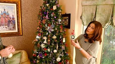Donna Buthmann decorates the tree at home in