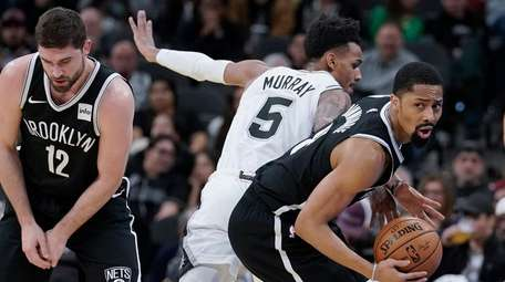 Nets' Spencer Dinwiddie, right, gets away from San