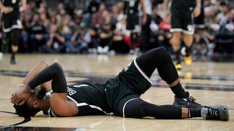 Brooklyn Nets' David Nwaba lies injured on the