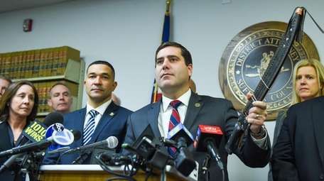 Suffolk County District Attorney Timothy Sini holds up