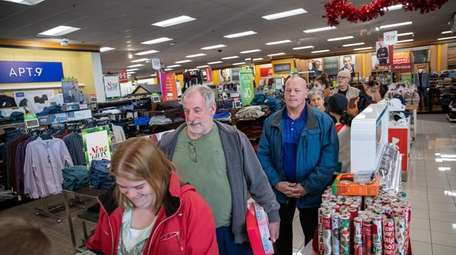 Last-minute shoppers wait in line Monday at a