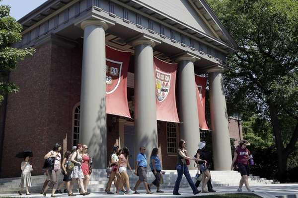 People tour Harvard University in Cambridge, Mass. Dozens