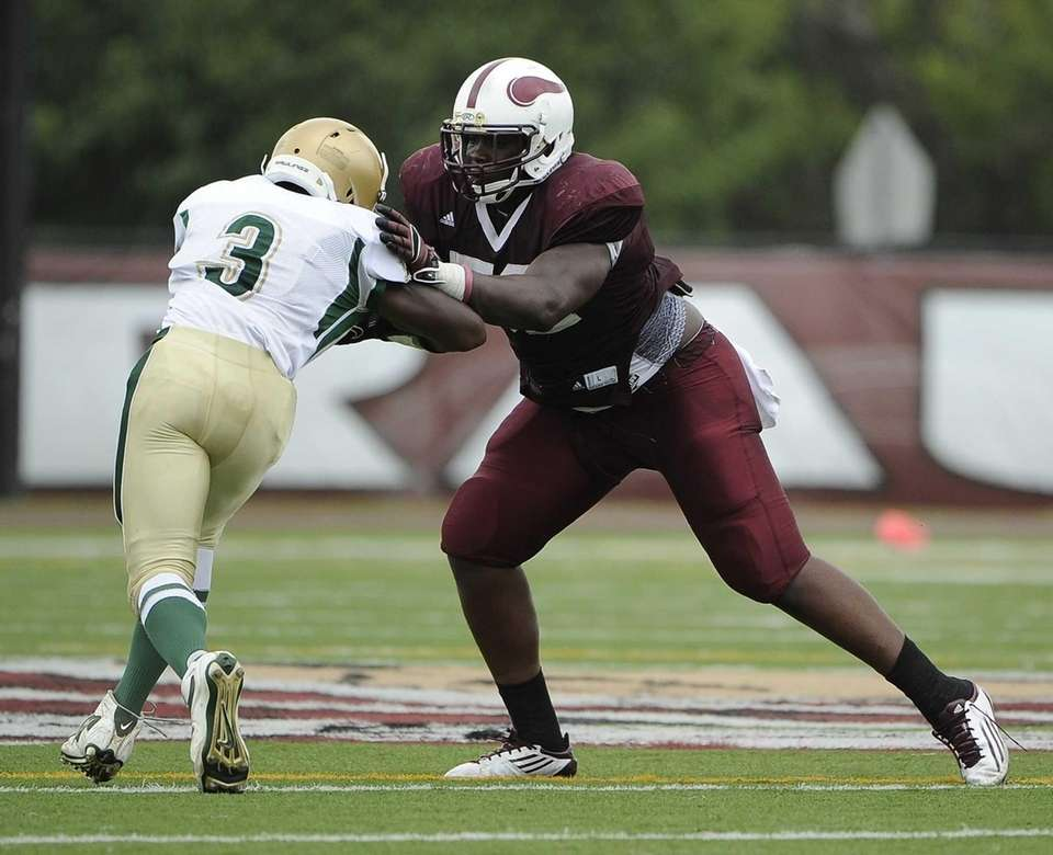 Bay Shore's Ousmane Camara tackles Longwood's Isiah White.