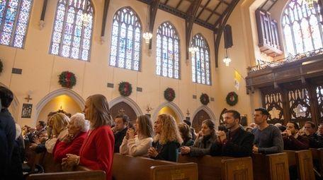 Parishoners pray during Christmas Mass at St. Agnes