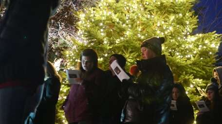 Parishioners sings Christmas carols in front of the