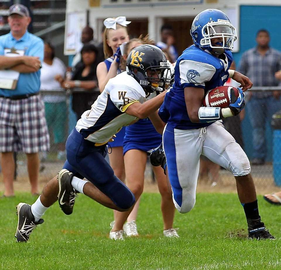 Riverhead RB Jeremiah Cheatom #20, goes up the