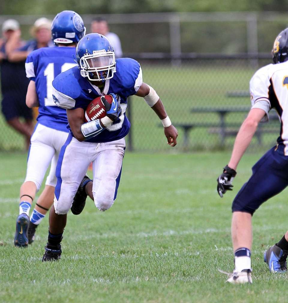 Riverhead RB Jeremiah Cheatom #20 gets the handoff,