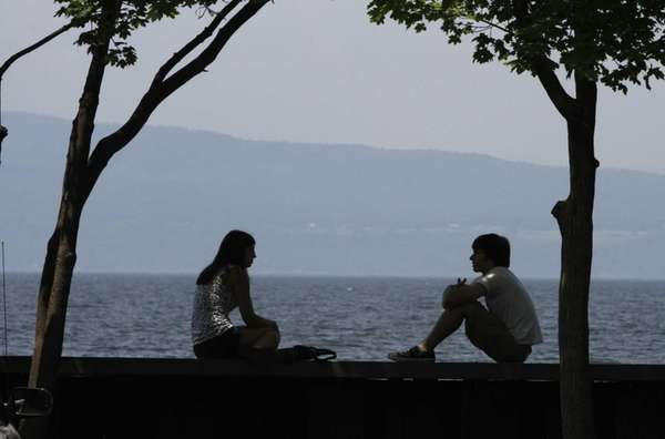 A couple enjoys the weather along Lake Champlain