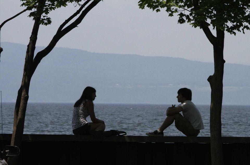 A couple enjoys the weather along Lake Champlain