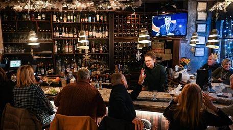 Patrons sit at the bar or dine at