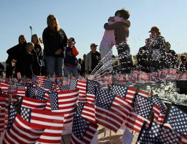 People embrace at memorial during ceremony at Point