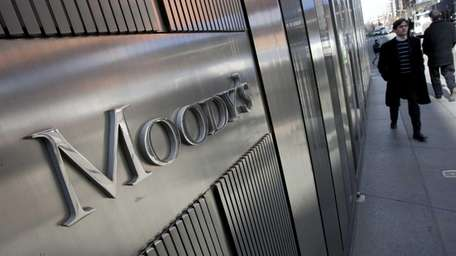 Pedestrians walk past the Moody's Investors Service headquarters