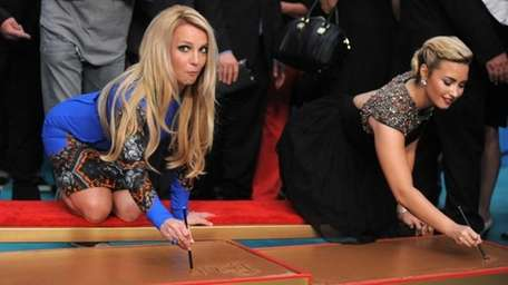 Judges Britney Spears, left, and Demi Lovato sign