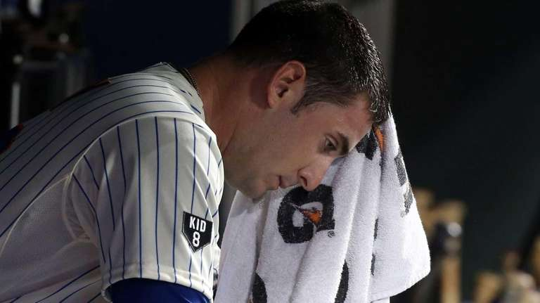 Matt Harvey sits in the dugout after leaving