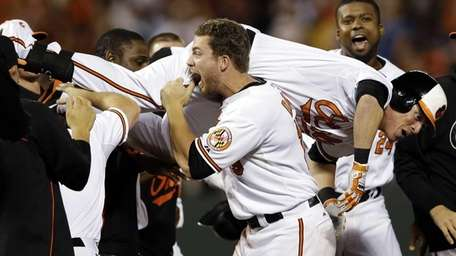 The Baltimore Orioles' Chris Davis, center, carries Nate