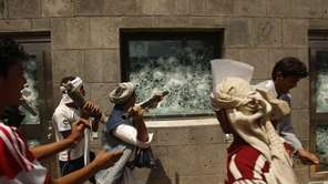 Yemeni protesters break a window of the U.S.