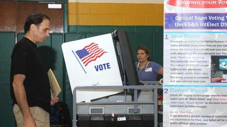John Prizzi watches as his ballot goes into