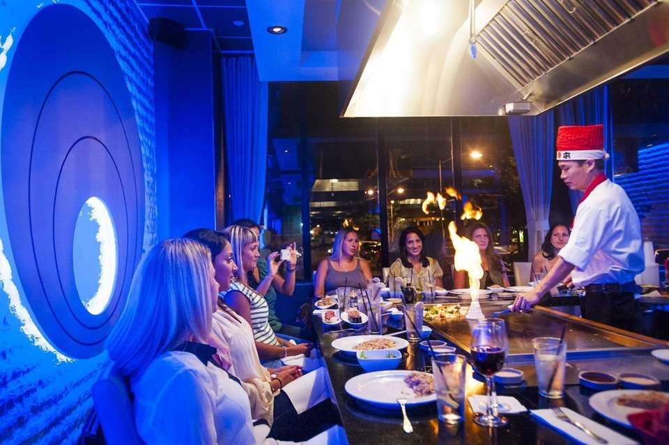A group of diners watches a hibachi chef